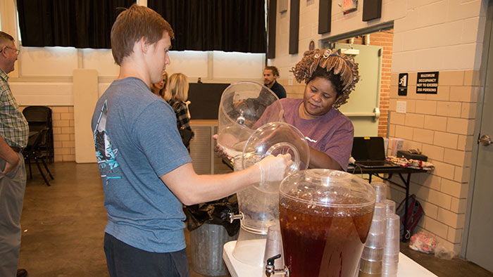 Health Promotion and Wellness Management students filling up water and tea to serve to people.